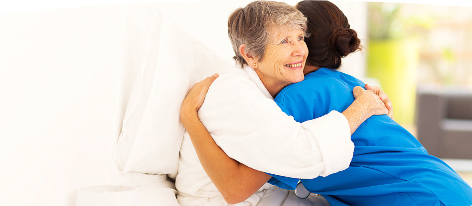 caregiver hugging an elderly woman