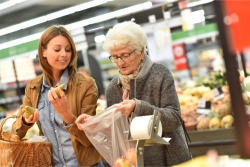 elderly woman doing grocery shopping with a caretaker
